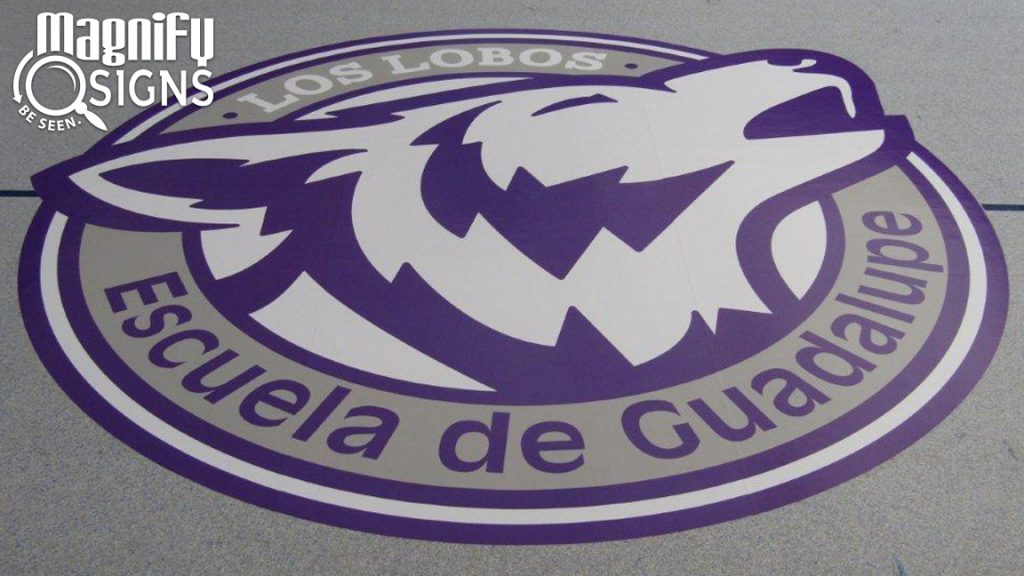 "Custom Circular Vinyl Print of the ""Los Lobos"" placed on the gym floor or Escuela de Guadalupe school in Denver, CO"